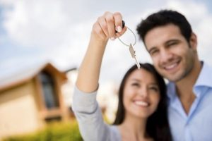 Couple holding house keys and looking very happy